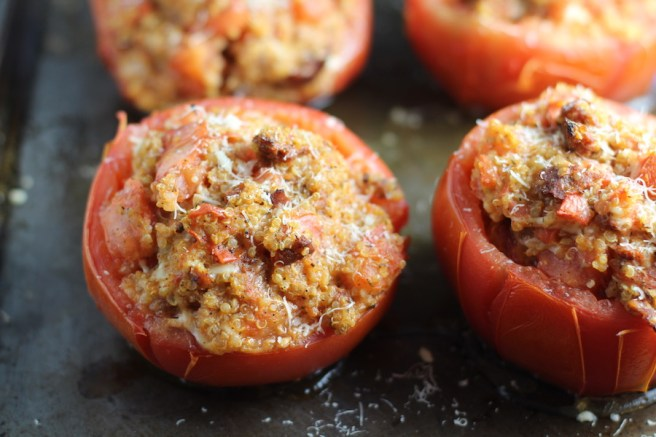 Stuffed Tomatoes on sheet pan on counter with chorizo, quinoa, parmesan cheese, chives, garlic, and oregano are simply divine!