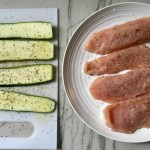 Raw zucchini slices and chicken breasts seasoned for Chicken Parmesan Pasta Bake. It cooks entirely in one casserole dish, including the pasta! Shell pasta in flavorful, tangy tomato sauce is topped with zucchini, chicken, mozzarella, parm, and crunchy breadcrumb topping.