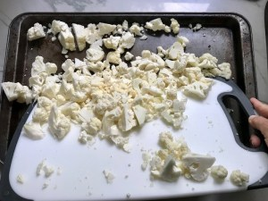 Dumping chopped cauliflower from cutting board onto sheet pan for Roasted Garlic Cauliflower Mash.