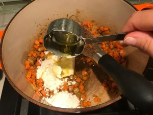 Flour being added to carrots and onions in pot for Creamy Chicken Sausage and Tortellini Soup. It's silky and creamy with onions, garlic, Chicken sausage, and zucchini bring so much flavor and texture.  The tortellini give that delicious salty, creamy, hearty bite!