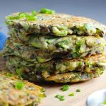 Lentil and Zucchini Cakes stacked on wood cutting board. They have a crispy outside and soft inside and are perfect for an easy dinner!  The flavors are simple but perfect with parmesan, oregano, scallions, lentils, and zucchini.