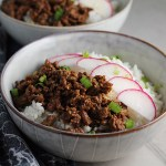 Korean Ground Beef and Rice Bowls with sliced radishes fanned out on top and scallion garnish.