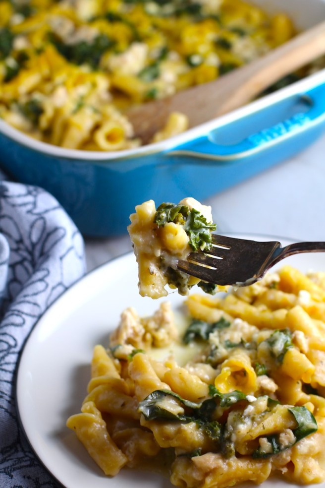 Fork with bite of Glorious Greek Ground Chicken Pasta Casserole with plate below and casserole in background. It has lean ground chicken with garlic, oregano, parmesan, feta and Kale.