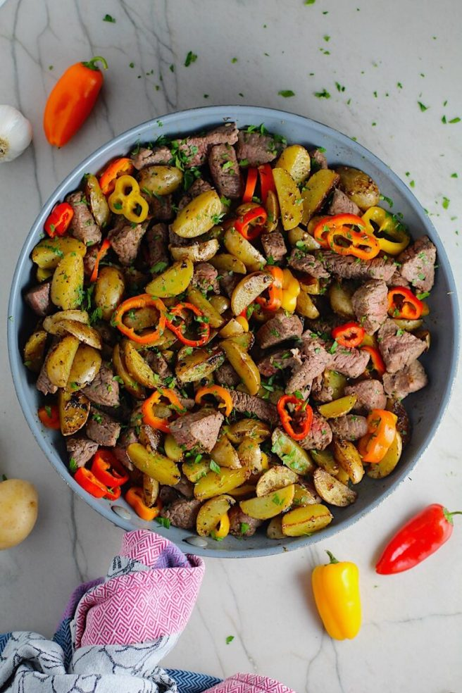 Garlic Potato and Steak Bites Recipe with sweet pepper slices in a pan on counter. It's an easy and delicious, one-pan family dinner!  You get fantastic salty, buttery, tender steak and potatoes in each and every mouthwatering bite!