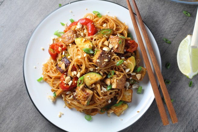 Thai Peanut Sauce Noodles with seared tofu and veggies on a plate with chopsticks.