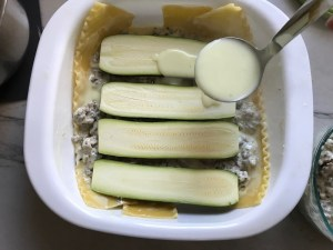 Ladle pouring white sauce over zucchini slices on top of beef and lasagna noodles in dish for White Lasagna Recipe with Zucchini and Ground Beef