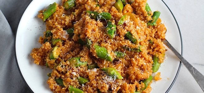 Asparagus and Tomato Quinoa Risotto with parmesan on top on a plate with fork.
