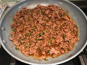 Cooked ground beef in pan for Taco Quinoa Bowl with Ground Beef, corn, cotija cheese, tomatoes, fresh cilantro, and cilantro lime crema