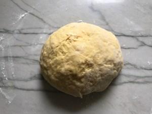 dough ball on floured counter for Easy Homemade Pasta recipe.