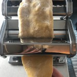 Thick piece of pasta dough going through the pasta roller with hand catching the dough at the bottom for Easy Homemade Pasta recipe.