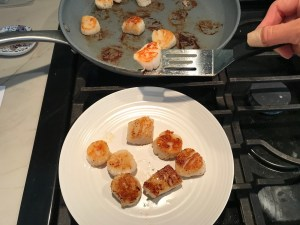 Seared scallops being transferred by spatula from pan to plate for Glazed Pan Seared Scallops with Garlic and Honey.