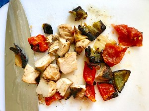 Grilled chicken, green peppers, tomatoes, and onions cut into pieces on a cutting board for Grilled Teriyaki Chicken Salad..