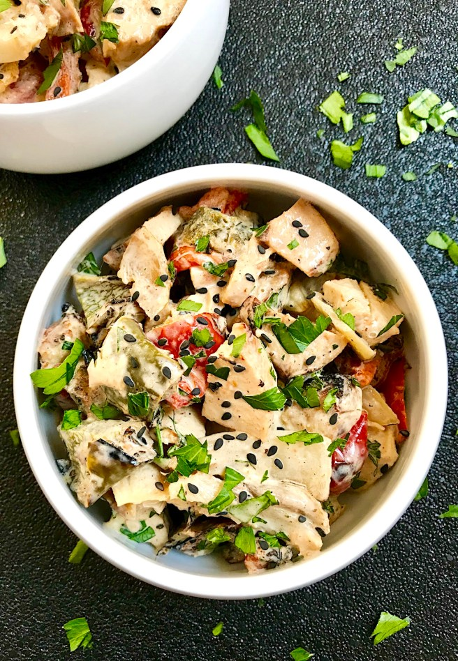 Grilled Teriyaki Chicken Salad in a bowl on black background with chicken, green peppers, tomatoes, onions, black sesame seeds, and cilantro.