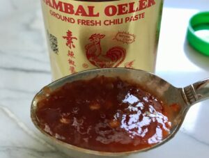 Bottle of Sambal Oelek chili paste with a spoonful in front for Dan Dan Noodle Recipe with Ground Chicken.