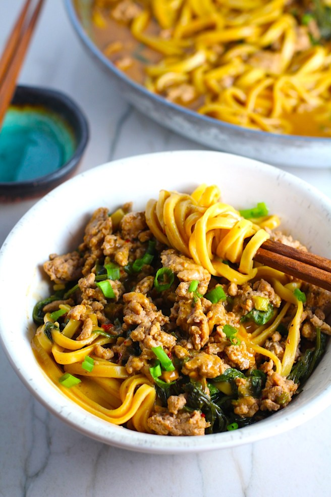 Dan Dan Noodle Recipe with Ground Chicken in a bowl.  Chopsticks have noodles wrapped around and scallion slices are on top.  The pan of noodles is in background.