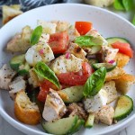 Toasted bread cubes, chicken, tomatoes, cucumber, basil, and mozzarella in a bowl for this Chicken Panzanella Salad Recipe. It's absolutely delicious.