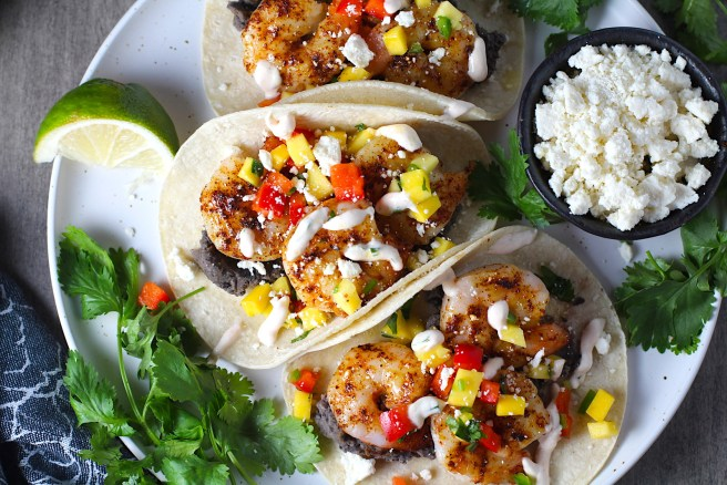 Grilled Shrimp Tacos in corn tortillas on a plate with Mango Salsa & Chipotle Crema. On the side are bowls of cotija cheese, crema, salsa, and cilantro leaves.