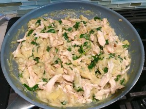 Spinach Artichoke Chicken filling in a large pan on stove for stuffing into pitas and then grilling.