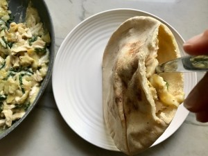 Spoon adding Spinach Artichoke Chicken filling to a cut open pita with pan of filling off to the side.