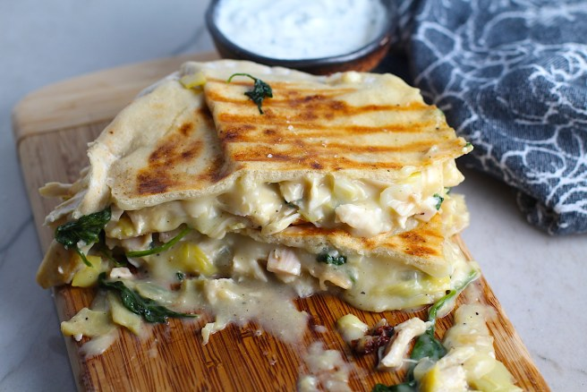 Spinach Artichoke Chicken Stuffed Pita is grilled and cut in half, then stacked on a wood platter with filling oozing out. In the back is a small bowl of crema.