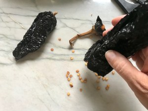 Hand shaking seeds out of dried ancho chile for Birria Tacos. This Birria Tacos Recipe in the Slow Cooker has shredded beef and Oaxaca cheese melted together in corn tortillas in a pan.