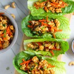 4 Cashew Chicken Lettuce Wraps on counter with a bowl of Cashew Chicken and Carrot filling on left and sauce on right.