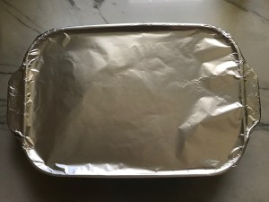 Aluminum foil covering a casserole dish for Chicken Wild Rice Casserole with Zucchini and Mushrooms.