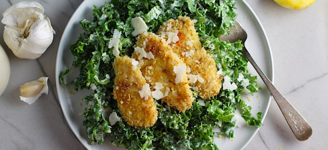 Kale Caesar Salad with Baked Crispy Lemon Chicken strips on top on a plate with a fork.