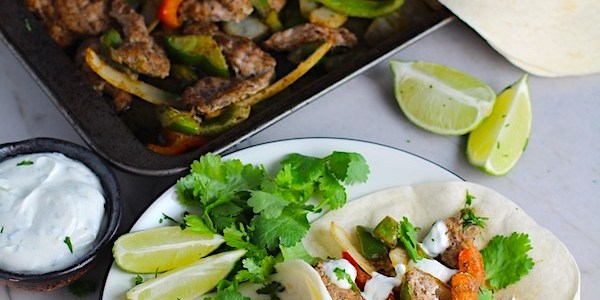 Sheet Pan Pork Fajitas Recipe with red pepper, green pepper, and onion, in flour tortillas on a plate. Topped with Cilantro Lime Crema, fresh cilantro leaves, and lime wedges. Sheet pan with pork, peppers, and onions in background along with crema and tortillas.