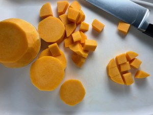 Butternut squash on cutting board, cut into round discs and then cubed for Crispy Sage Chicken, Butternut Squash, and Shallots.