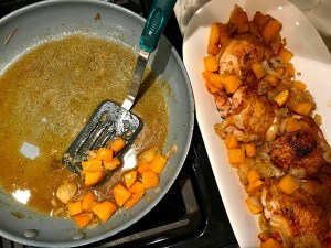 Spatula scooping butternut squash cubes and shallots from a frying pan next to platter with chicken for Crispy Sage Chicken, Butternut Squash, and Shallots.