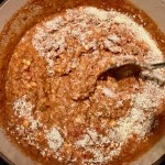 Spoon mixing parmesan cheese into pot of ground beef and tomato-chile sauce for Southwestern Pasta with Ground Beef and Corn and breadcrumbs. The sauce is thick and hearty with ground beef, sweet corn kernels, chunky tomatoes, chipotle peppers in adobo, green chiles, parmesan cheese, and lots of smokey and spicy seasonings.