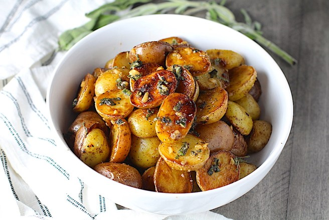 Crispy browned Sage Butter Potatoes in a bowl with garlic, sage butter glistening on top.