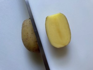 Knife cutting a creamer potato in half for Sage Butter Potatoes.