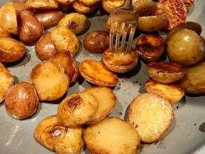 Browned and crispy halved red and gold creamer potatoes in a skillet with a fork in one potato for Sage Butter Potatoes.