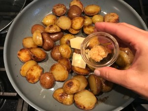 Hand adding minced garlic to skillet with 2 pats of butter and browned and crispy halved red and gold creamer potatoes for Sage Butter Potatoes.