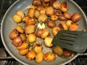 Browned and crispy halved red and gold creamer potatoes in a skillet with garlic, sage, and melted butter for Sage Butter Potatoes.