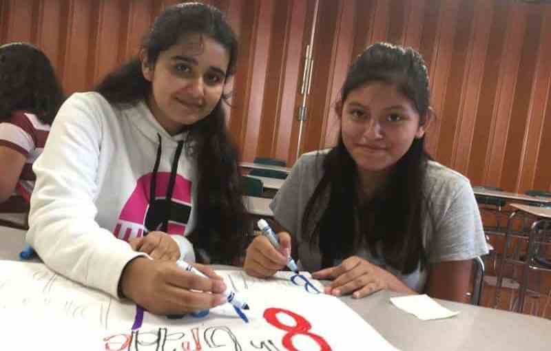 Isaac E. Young eighth graders Emelien Perez (left) and Lesly Paccha work on food drive posters.