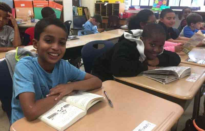 Webster fourth-grader Rohan Ross (left), Anthony Guimaras and classmates enjoy a book of their choice as the readathon begins.