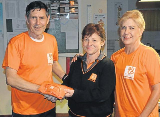 GRATEFUL FOR SPONSORSHIP: Kowie Striders chairman Sticks Stiglingh, left, and vice-chairwoman Frieda Greyling, right, accept T-shirts from Vanessa Gerber of sponsor Buco. Picture: JON HOUZET