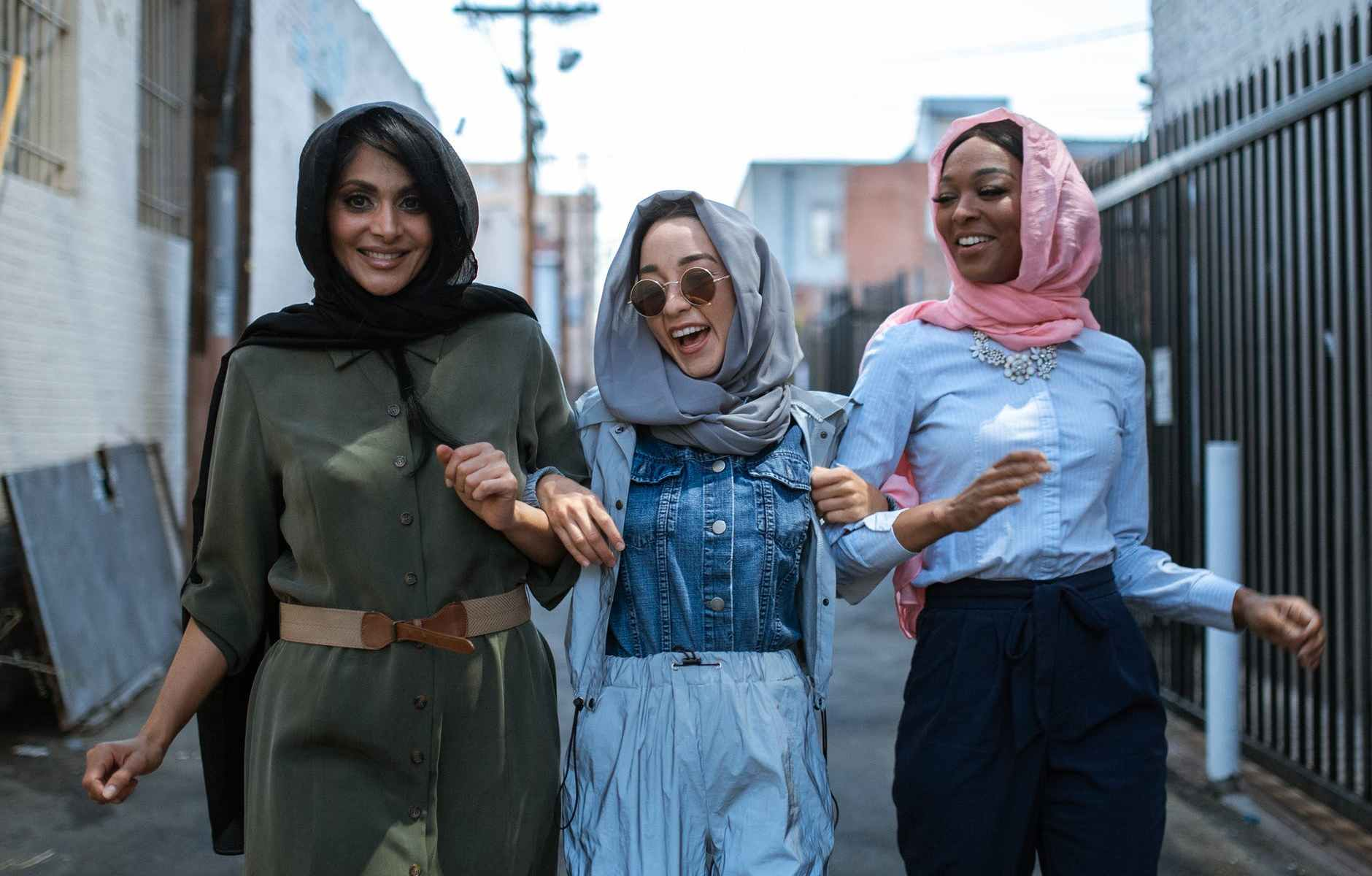 joyful multiethnic women in headscarves walking on street