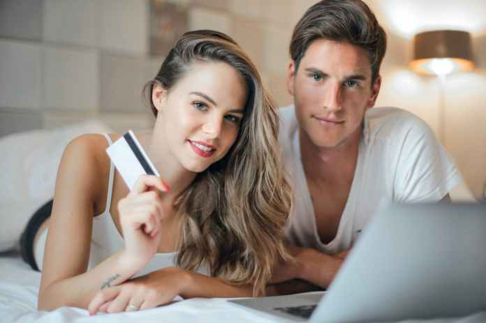 happy young couple doing purchase on internet together at home
