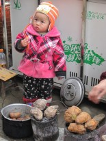 A cute little girl was at her parent's side selling sweet potatoes.