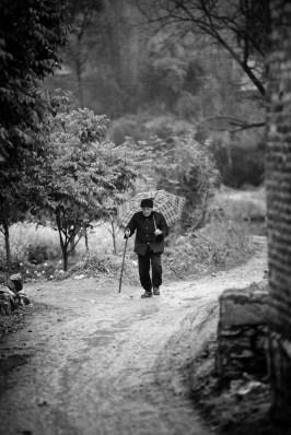 An elderly was walking back home.