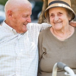 Senior Man smiles with his arm around his wife