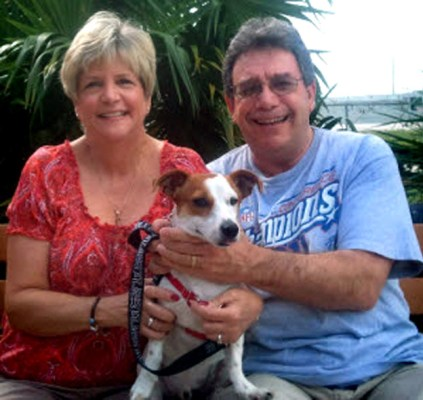 """Penny and Carey Sackener, pose with Charlie, who they adopted during the """"Get on Board"""" promotion in October."""