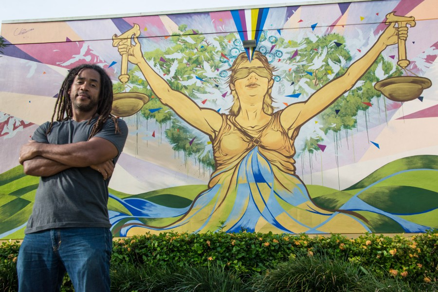"Ruben Ubiera in front of his mural ""Lady Justice"" - Photo by Sharon Aron Baron"
