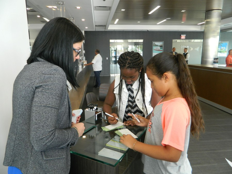BankUnited Learning & Development Facility Trainer Meghan Bussell helps students Dayna-Lee Polo and Ivanna Matta fill out deposit tickets.