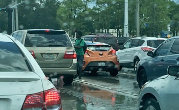 One of several teenagers selling candy in the rain on a dangerous Tamarac intersection.
