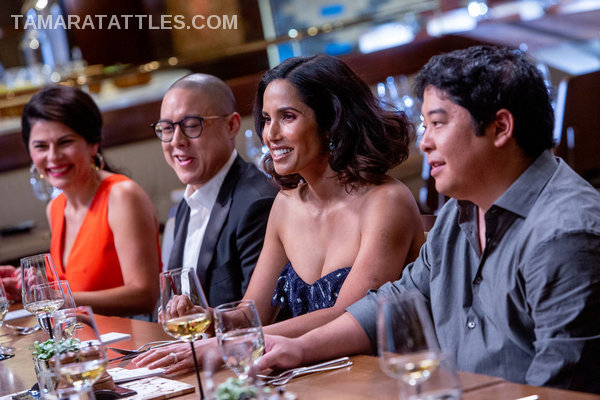 Padma smiling with a short wig at table with other judges